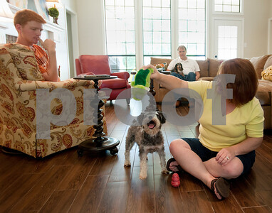 photo by Sarah A. Miller/Tyler Morning Telegraph  Francie Hodges of Tyler plays with her dog named Scout Friday July 12. Scout was a rescue dog and has been a member of the family since January. Also pictured is Francie Hodges' son Clayton, 17, left, and husband Bryan.