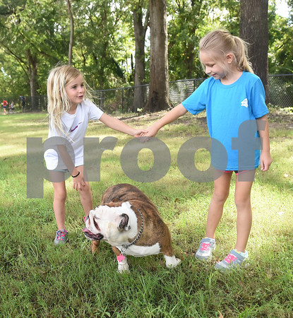 A dog walks between Rylee Phillips, 6, and Caroline Burkett, 6, as they visit the new Sunrise Paw Park, 114515 County Road 166, Baggett Road in Tyler. The new dog park has separate areas for large dogs and small dogs as well as drinking fountains and a dog wash station. The Tyler Sunrise Rotary Club and the Anderson-Vukelja Foundation collaborated on the project which was privately funded.   (Sarah A. Miller/Tyler Morning Telegraph)