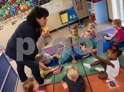 """Christian author Shelly Roark blows bubbles toward Taryn Jones, 2, before reading her children's book """"The Bubble Who Would Not Pop"""" to children in the early education program at Trinity Lutheran Church Friday Sept. 1, 2017.  (Sarah A. Miller/Tyler Morning Telegraph)"""
