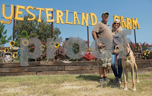 Chuck and Kama Bozeman and their dog Rudy are pictured at their business, Yesterland Farm, in Canton Thursday Sept. 14, 2017. Yesterland Farm offers family entertainment from a petting zoo to amusement park style rides and even a swamp zombie paintball area.  (Sarah A. Miller/Tyler Morning Telegraph)