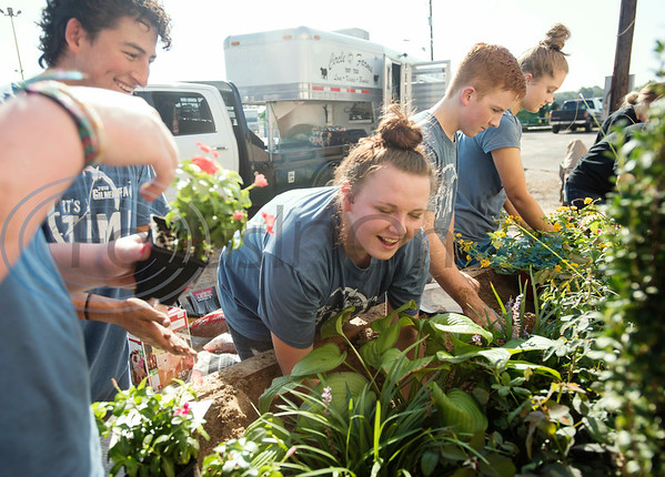 Gilmer High School's junior Cathrine Bennett, 16, laughs, as she places a plant into the dirt during the Horticulture Show Landscape Design Competition at the East Texas State Fair on Wednesday Sept. 19, 2018. Teams from local high schools competed in designing and making a themed 4 foot by 7 foot planter box.  (Sarah A. Miller/Tyler Morning Telegraph)