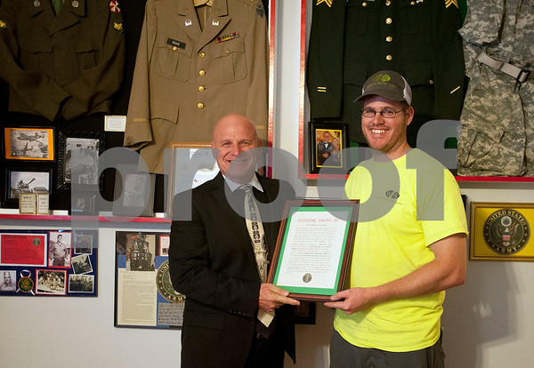Military resource coordinator Keith Irwin gives his son-in-law Rushing Smith III a plaque commemorating his years of service during an open house event at The Green Zone in Tyler. The Green Zone is a resource center for veterans ran by veterans. Located at 512 Charnwood in Tyler, The Green Zone is open with peer councilors available from 9 a.m. to 5 p.m.   (Sarah A. Miller/Tyler Morning Telegraph)