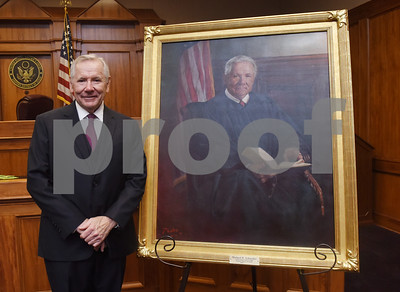 United States District Judge for the Eastern District of Texas Michael Schneider has his photo taken with a portrait of himself by artist Dean Paules during his retirement reception in Tyler Friday Sept. 23, 2016.   (Sarah A. Miller/Tyler Morning Telegraph)