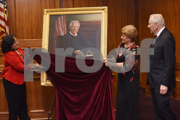Rosa Ferguson and Linda Pritchard unveil a portrait by artist Dean Paules for United States District Judge for the Eastern District of Texas Michael Schneider during his retirement reception in Tyler Friday Sept. 23, 2016.   (Sarah A. Miller/Tyler Morning Telegraph)
