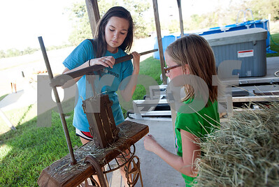 Kara Pinkerton, 13, and her sister Reese Pinkerton, 8, make mini hay bales at their home in Chapel Hill to be given to buyers at the annual East Texas State Fair Hay Show. The Pinkertons are preparing their animals to be shown at the Junior Livestock show at the East Texas State Fair, which starts Sept. 25 in Tyler.   (Sarah A. Miller/Tyler Morning Telegraph)