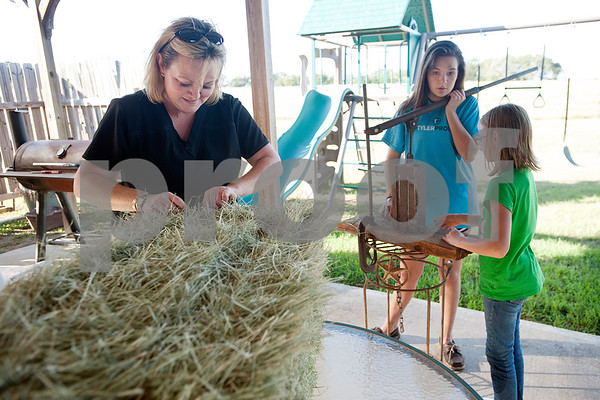 Roxy Pinkerton helps her daughters Kara Pinkerton, 13, and Reese Pinkerton, 8, make mini hay bales at their home in Chapel Hill to be given to buyers at the annual East Texas State Fair Hay Show. The Pinkertons are preparing their animals to be shown at the Junior Livestock show at the East Texas State Fair, which starts Sept. 25 in Tyler.   (Sarah A. Miller/Tyler Morning Telegraph)