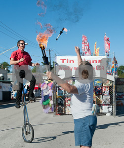 photo by Sarah A. Miller/Tyler Morning Telegraph  Entertainer Wade Henry has audience volunteer Tim Phifer of Tyler toss him a fire stick while he rides a six foot tall unicycle during his show at the East Texas State Fair Wednesday. Henry is known for his comedic unicycle acts, and he is also a juggler.