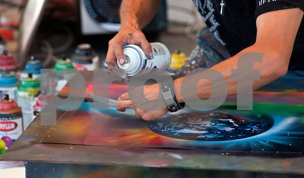 """photo by Sarah A. Miller/Tyler Morning Telegraph  """"Cosmo"""" Martin Martinez of Dallas uses paper and spray paint to create art at the East Texas Fair Wednesday in Tyler. Martinez's style of painting can be described as performance art. His pieces are for sale at his booth at the fair."""
