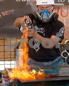 "photo by Sarah A. Miller/Tyler Morning Telegraph  ""Cosmo"" Martin Martinez of Dallas uses fire to heat a spray paint painting he created at the East Texas Fair Wednesday in Tyler. Martinez's style of painting can be described as performance art. His pieces are for sale at his booth at the fair."