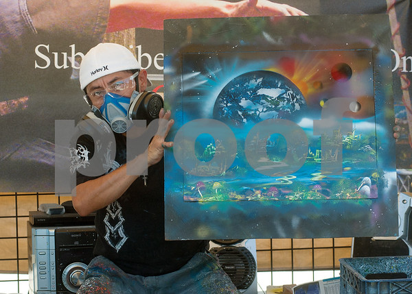 photo by Sarah A. Miller/Tyler Morning Telegraph  Martin Martinez of Dallas holds up a newly finished spray paint artwork that he makes under the name Cosmo Universal Art. He has a vendor booth at the East Texas Fair in Tyler where he creates and sells his pieces.