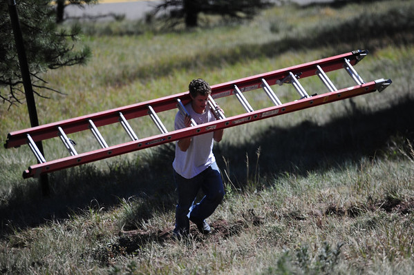 CJ Reynolds carries a ladder up the hill to help repair the damage to the Flagstaff Star in Boulder, Colorado September 28, 2012.  Reynolds has volunteered his time for a decade to keep the Flagstaff Star lit. DAILY CAMERA/ MARK LEFFINGWELL