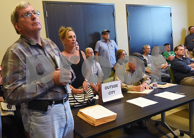 Liberty Utilities customers, including David Fenter, left, line the back of the room as they attend a town hall meeting held Wednesday night at the Faulkner Park Police Substation. Earlier this month, Liberty Utilities proposed rates that would more than triple some customers' monthly bills for wastewater service by next March.  (Sarah A. Miller/Tyler Morning Telegraph)