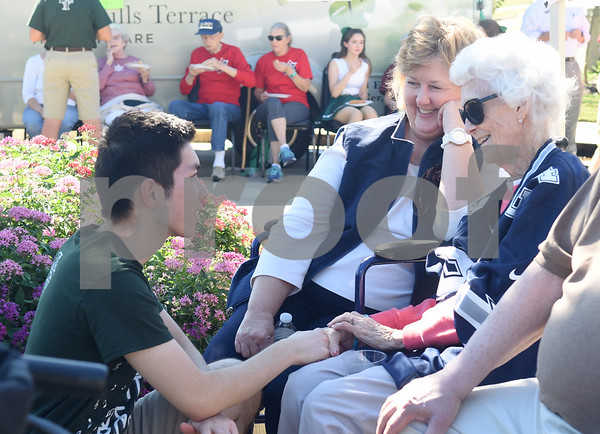 Bishop T.K. Gorman Catholic High School band member Hans Li talks with resident Virginia Alexander and her daughter Ginger Clayborn during a tailgate at Oak Hill Terrace Memory Care in Tyler Friday afternoon Sept. 30, 2016. Bishop Gorman football players, cheerleaders, band members and Crusaderettes performed and socialized with residents of Oak Hill Terrace Memory Care during the tailgate party.  (Sarah A. Miller/Tyler Morning Telegraph)