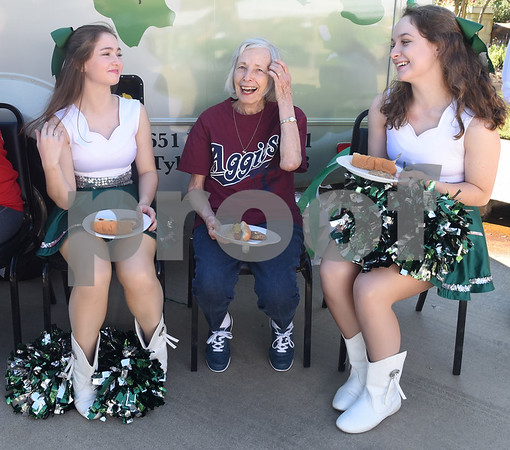 Bishop T.K. Gorman Catholic High School Crusaderette dance team members Kathleen Bochow, left, and Elizabeth McKnight, right, eat lunch with resident Jackie Washout, center, during a tailgate at Oak Hill Terrace Memory Care in Tyler Friday afternoon Sept. 30, 2016. Bishop Gorman football players, cheerleaders, band members and Crusaderettes performed and socialized with residents of Oak Hill Terrace Memory Care during the tailgate party.  (Sarah A. Miller/Tyler Morning Telegraph)