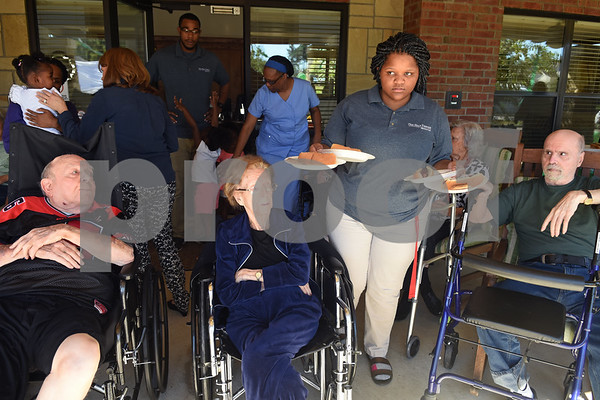 Caregiver Lindsey Tave passes out hit dog lunches to residents at Oak Hill Terrace Memory Care in Tyler Friday afternoon Sept. 30, 2016 during a tailgate with Bishop T.K. Gorman high schoolers. Bishop Gorman football players, cheerleaders, band members and Crusaderettes performed and socialized with residents of Oak Hill Terrace Memory Care during the tailgate party.  (Sarah A. Miller/Tyler Morning Telegraph)