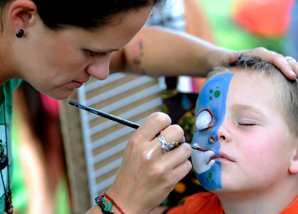 Makalu Bowen keeps his eyes closed while Amber Jarvis paints his face at the Boulder Creek Hometown Fair in Boulder, Colorado September 5, 2011.   CAMERA/Mark Leffingwell