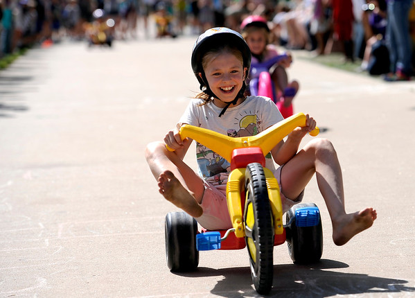 Katie Megerle, 10 sticks out her feet as she wins her heat in the big wheel races at the Boulder Creek Hometown Fair in Boulder, Colorado September 5, 2011.   CAMERA/Mark Leffingwell