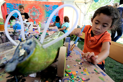 Olivia Gray, 5, adds some color to the wheels of her zucchini racer at Boulder Creek Hometown Fair in Boulder, Colorado September 5, 2011.   CAMERA/Mark Leffingwell
