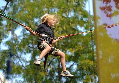 Slooane MacBride (cq), 9, soars 20 feet in the air on the Bungee Tramp at Boulder Creek Hometown Fair in Boulder, Colorado September 5, 2011.   CAMERA/Mark Leffingwell
