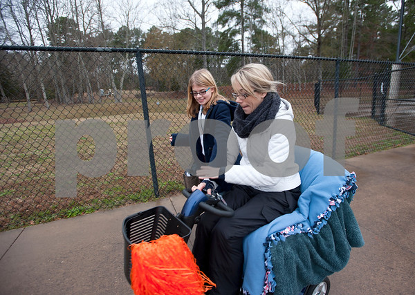 photo by Sarah A. Miller/Tyler Morning Telegraph  Christi Wyatt Zimmerman, 37, races her step daughter Jaydan Zimmerman, 12, in her motorized chair named Scoot after attending a soccer game for her son Jordan Wyatt at The Brook Hill School's Herrington Stadium Jan. 10, 2015. Christi Wyatt Zimmerman, 37, uses the chair instead of walking because her muscles are wear from amyotrophic lateral sclerosis, known commonly as ALS.