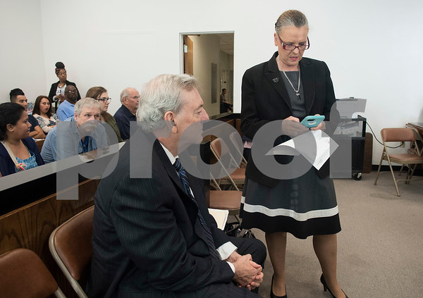 Attorney Don Kent assists his wife attorney Cynthia Kent as she works at a child support hearing the Smith County Courthouse July 11, 2017. Mr. Kent is in the beginning stages of Lewy Body Dementia and is in the process of retiring from his law career. Lewy Body Dementia is the second most common type of dementia. Mrs. Kent is a retired State District Judge.  (Sarah A. Miller/Tyler Morning Telegraph)