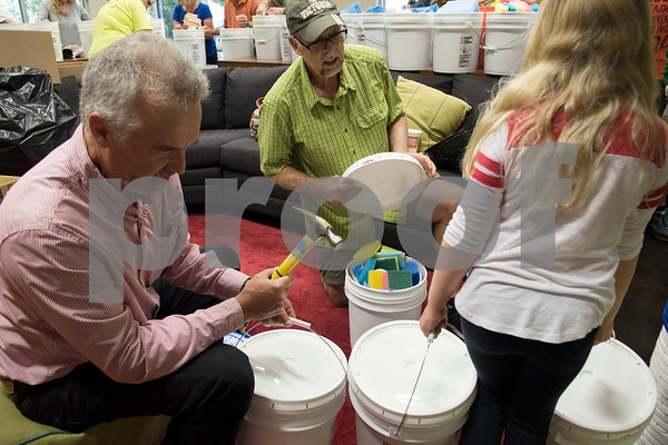 Volunteers Steve Comer and Bill Pulliam close flood buckets to send to Hurricane Harvey victims made at Dayspring United Methodist Church in Tyler Thursday Sept. 7, 2017. The large buckets contained household items like dish soup, cleaning cloths, sponges and cleaning brushes.  (Sarah A. Miller/Tyler Morning Telegraph)