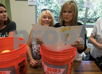 Karol Cornelius and Betty Paul read a sympathy card made by a child before placing it in a bucket during a flood bucket making event at Dayspring United Methodist Church in Tyler Thursday Sept. 7, 2017. The large buckets contained household items like dish soup, cleaning cloths, sponges and cleaning brushes and will be given to people who are cleaning up their houses after flood damage from Hurricane Harvey.  (Sarah A. Miller/Tyler Morning Telegraph)