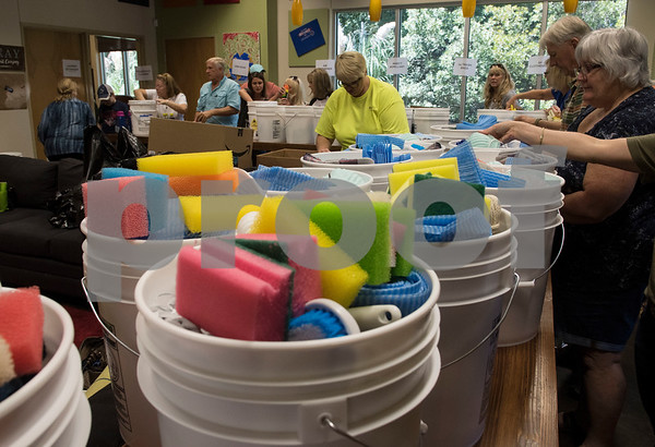Volunteers make flood buckets to send to Hurricane Harvey victims at Dayspring United Methodist Church in Tyler Thursday Sept. 7, 2017. The large buckets contained household items like dish soup, cleaning cloths, sponges and cleaning brushes.  (Sarah A. Miller/Tyler Morning Telegraph)