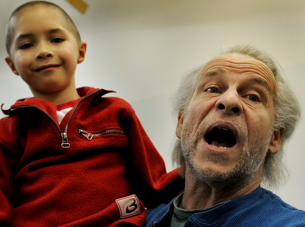 """Bob Buckley, playing the part of """"Scrooge"""", holds """"Tiny Tim"""" played by Addison Kleinhans during a rehearsal for """"A Christmas Carol"""" on Thursday, Nov. 18, at the Carlson Gymnasium on the University of Colorado campus in Boulder.<br /> Jeremy Papasso"""