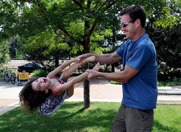 "Brianna Heron, 5, plays with her father, Matt, Saturday in downtown Louisville.<br /> For more photos of Louisville, go to  <a href=""http://www.dailycamera.com"">http://www.dailycamera.com</a>.<br /> Cliff Grassmick / July 7, 2012"