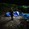 KRISTOPHER RADDER — BRATTLEBORO REFORMER<br /> Brattleboro Police Officer Brad Penniman uses a flashlight as he looks around a tent encampment under the Elm Street Bridge on Sept. 5, 2018.