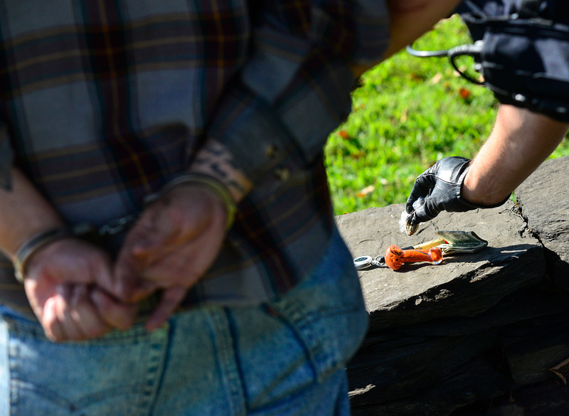 KRISTOPHER RADDER — BRATTLEBORO REFORMER<br /> Brattleboro Police Officer Brad Penniman pulls out a bag of weed from a person's pocket after arresting them for an outstanding warrant for a missed court date on Sept. 5, 2018.