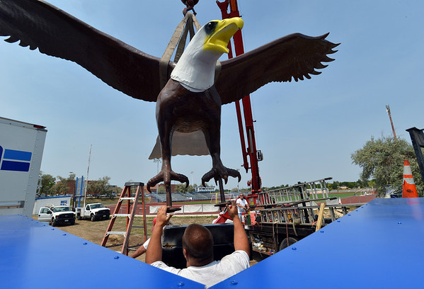 Tyler Scriven, with Freeman Signs, helps move the Bald Eagle sculpture onto it's base at Broomfield High School on the corner of Main St. and Eagle Way on Friday.<br />  August 17, 2012<br /> staff photo/ David R. Jennings
