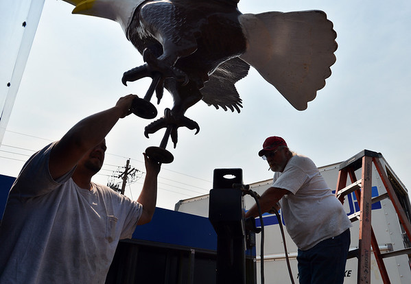 Tyler Scriven, left, and Stan Scriven, with Freeman Signs, begin to move the Bald Eagle sculpture onto it's base at Broomfield High School on the corner of Main St. and Eagle Way on Friday.<br />  August 17, 2012<br /> staff photo/ David R. Jennings