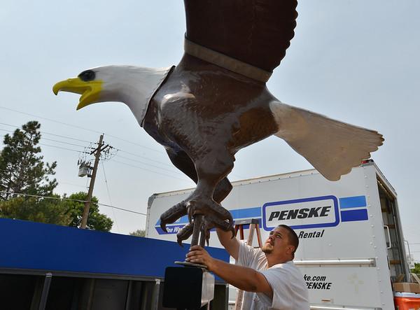 Tyler Scriven, with Freeman Signs, holds the Bald Eagle sculpture in place on it's base at Broomfield High School on the corner of Main St. and Eagle Way on Friday.<br />  August 17, 2012<br /> staff photo/ David R. Jennings