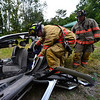 "KRISTOPHER RADDER - BRATTLEBORO REFORMER<br /> Brattleboro Firefighter Matt Hubbard uses the new ""Jaws of Life"" cutting tool while firefighter Al Olney watches."