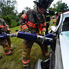 "KRISTOPHER RADDER - BRATTLEBORO REFORMER<br /> Brattleboro Firefighter George Allen uses the ""Jaws of Life,"" cutting tool to cut the hinges while crews train on the new equipment."