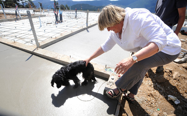 "Andi O'Conor has her dog Nellie walk across the newly laid concrete slab of her new home. O'Conor lost her home in the Fourmile Fire.<br /> FOR A VIDEO AND MORE PHOTOS OF ANDI MAKING HER ARTWORK GO  TO  <a href=""http://WWW.DAILYCAMERA.COM"">http://WWW.DAILYCAMERA.COM</a> <br /> Photo by Paul Aiken / The Camera / August 29 2011"