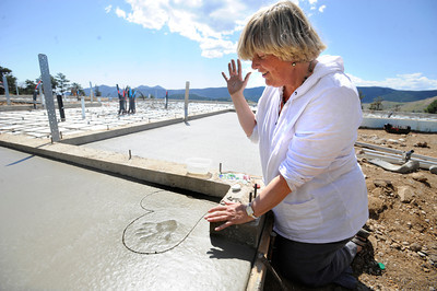 Andi O'Conor puts her handprint in the newly laid concrete slab of her new home. O'Conor lost her home in the Fourmile Fire. FOR A VIDEO AND MORE PHOTOS OF ANDI MAKING HER ARTWORK GO  TO WWW.DAILYCAMERA.COM  Photo by Paul Aiken / The Camera / August 29 2011