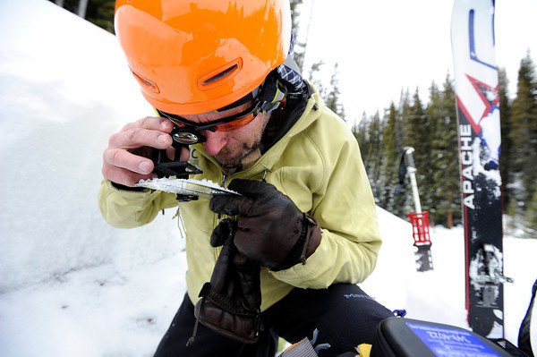 "Scott Toepfer uses a magnifying glass and a crystal card to inspect the base layer of snow after digging a snow pit to observe current snow conditions on Wednesday, Feb. 22, on Wheeler Trail in Breckenridge. Toepfer works for the Colorado Avalanche Information Center and was heading to Francie's Cabin to check conditions above tree line. For more photos and video of the avalanche forecasting go to  <a href=""http://www.dailycamera.com"">http://www.dailycamera.com</a><br /> Jeremy Papasso/ Camera"