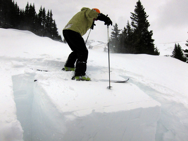 Scott Toepfer, Avalanche Forecaster with Colorado Avalanche Information Center, steps onto a block of snow for a Reutschblock test to evaluate the snow's strength under a skier's weight during a day analyzing the snowpack in the Crystal Creek Drainage area above Breckenridge Colorado on February 22, 2012. <br /> Photo by Jenn Fields / The Camera / Boulder