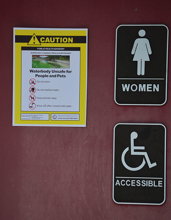 GILLIAN JONES — THE BERKSHIRE EAGLE<br /> A few signs, including this one on the restrooms at Pontoosuc's boat launch warned visitors of a possible algae bloom which prompted health officials to close Pontoosuc Lake on Friday. Officials lifted the advisory Monday afternoon after tests for cyanobacteria bloom where completed.