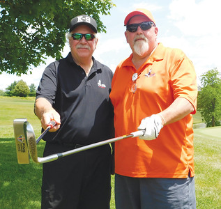JONATHAN DELOZIER / GAZETTE Mike Schmock of Medina, left, coaches Columbus resident Tim Jackson on Wednesday in this year's American Blind Golf Championship, held at Hawk's Nest Golf Club in Creston.