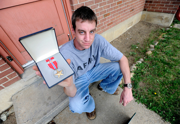 """University of Colorado student Jonathan Wezner holds his bronze star that he was awarded for the intelligence work he did in Afghanistan while serving in the Army on Wednesday, April 18, in Boulder. For more photos and video of the life of Wezner go to  <a href=""""http://www.dailycamera.com"""">http://www.dailycamera.com</a><br /> Jeremy Papasso/ Camera"""
