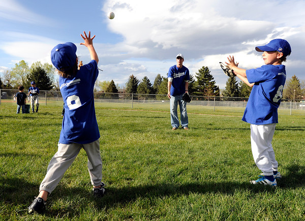 "University of Colorado student Jonathan Wezner plays catch with Addison Dec., 6, left, and Bennett Viverito, 6, before the start of a tee-ball game on Wednesday, April 18, in Boulder. Wezner and his wife Amber coach the team. For more photos and video of the life of Wezner go to  <a href=""http://www.dailycamera.com"">http://www.dailycamera.com</a><br /> Jeremy Papasso/ Camera"