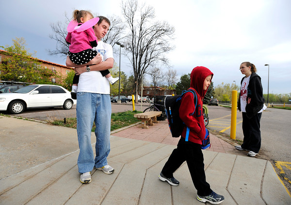 "University of Colorado student Jonathan Wezner holds his daughter Ashlyn, 2, as he watches his step-son Ayden, 7, head towards the school bus on Wednesday, April 18, near their apartment in Smiley Court in Boulder. For more photos and video of the life of Wezner go to  <a href=""http://www.dailycamera.com"">http://www.dailycamera.com</a><br /> Jeremy Papasso/ Camera"