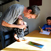 "University of Colorado student Jonathan Wezner wipes chocolate from the mouth of his daughter Ashlyn, 2, while his step son Ayden, 7, right, works on his spelling homework on Wednesday, April 18, at their house in Smiley Court in Boulder. For more photos and video of the life of Wezner go to  <a href=""http://www.dailycamera.com"">http://www.dailycamera.com</a><br /> Jeremy Papasso/ Camera"