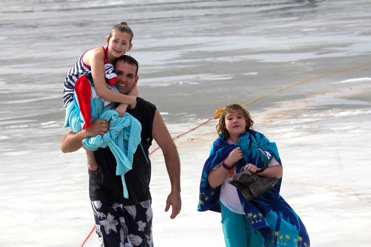 ALEC SMITH / GAZETTE Walking off the ice after Saturday's Polar Bear Jump at Chippewa Lake is Brad Winter, assistant fire chief of Medina, with Kailey O'Callaghan on his shoulder and Alyna Yagatich from Akron (right).