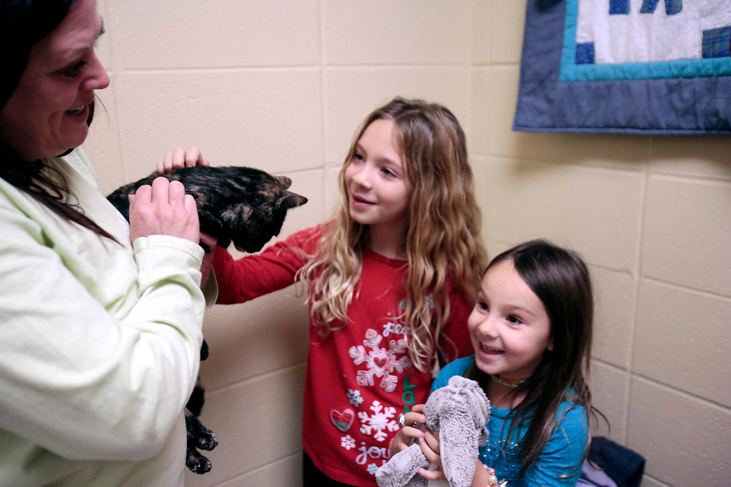 . Colleen McGrath hands over Skittles to Alex, 8, left, and Jordan Sotek, 5, her new adoptive family, at the Berkshire Humane Society in Pittsfield. Sunday, December 29, 2013. (Stephanie Zollshan   Berkshire Eagle Staff)