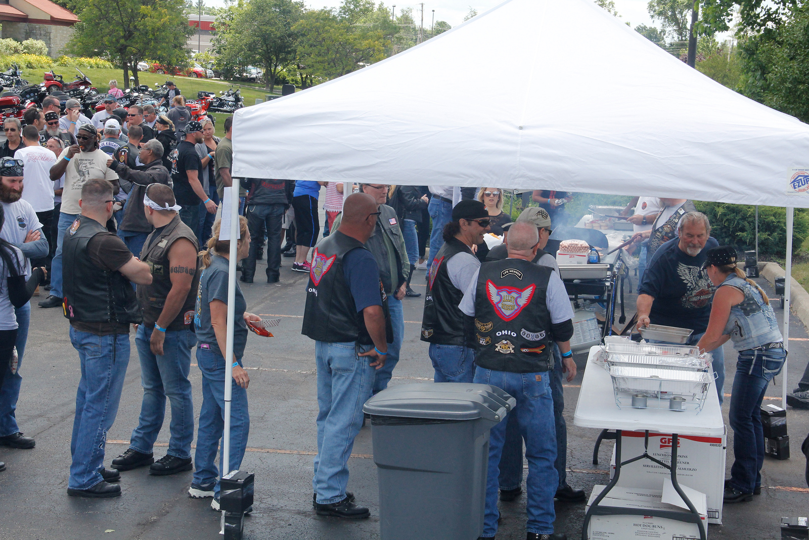 ALEC SMITH / GAZETTE Hundreds of motorcyclists participate Sunday in an event called Cops Ride, in which riders traveled about 54 miles through Cuyahoga, Lorain and Medina counties. The event ended at Stinger Harley-Davidson in Medina Township. At right, serving food after the ride are Tony Puchowicz from Elyria and Bobbi Havrilla from Wadsworth.